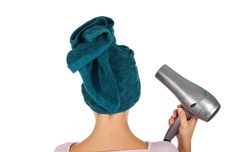 Smiling young woman with bathtowel on head holding a hair dryer on isolated background - back view