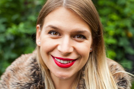 Close up portrait of a charming young lady wearing make up - red lips outdoor
