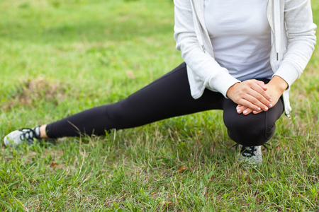 Young female warming up before workout in the park outdoor, stretching leg muscles