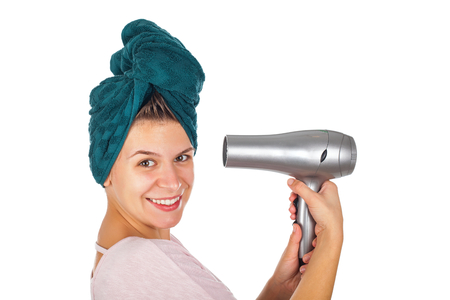 dryer: Smiling young woman with bath towel on head holding a hair dryer - isolated background