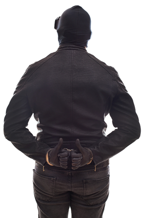 Back view angerous criminal wearing black clothes and mask with handcuffs on isolated background Stock Photo