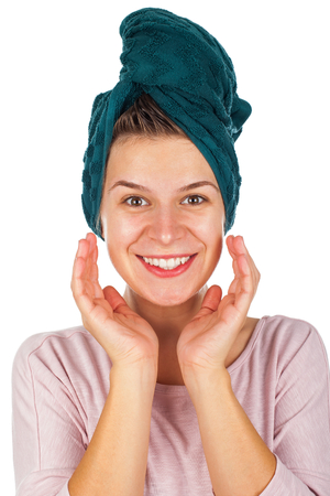Happy young woman with towel on head applying facial moisturizer after shower Stock Photo