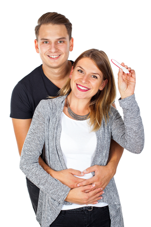 Pregnancy test positive, happy couple embracing on isolated background