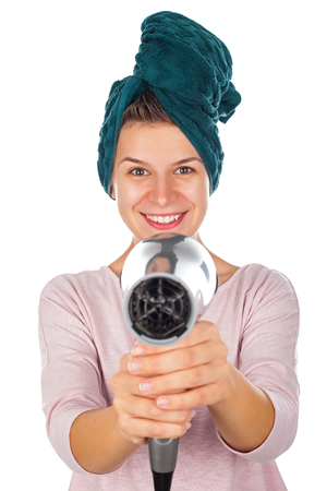 Happy smiling female with bath towel on head holding a hair dryer - isolated background