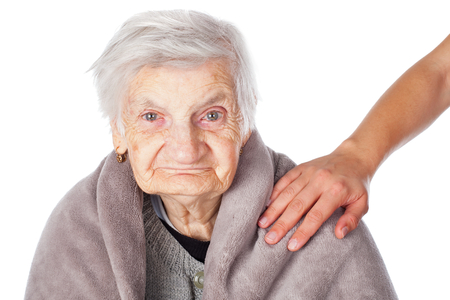 caregivers: Senior ill woman on isolated covered by a warm blanket caregivers helping hands