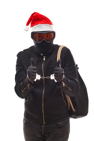 Arrested thief wearing mask and santa claus cap with handcuffs on isolated background Imagens