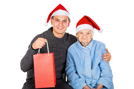 Picture of an old lady receiving Christmas gifts from her grandson