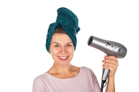 Smiling young woman holding a blow dryer after bath on isolated background