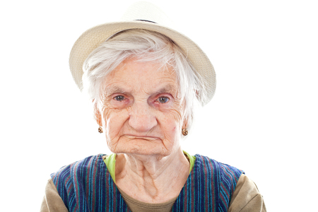 Picture of a disabled senior woman sitting indoors and  wearing a hat Stock Photo