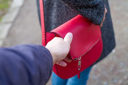 Close up picture of woman holding her red bag while a thief trying to steal from her