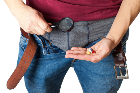Close up picture of mans crotch with unzipped jeans holding potency pills and enlarged viewer