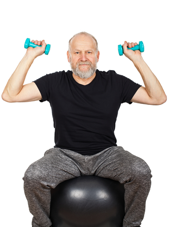 Senior bearded man doing fitness exercises with dumbbells and fitness ball on isolated background