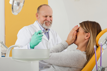 Scared female patient before dental procedure and male doctor holding local anesthetic injection