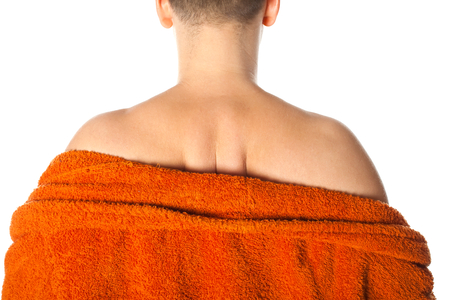 Young man having severe backache posing in bathrobe after shower, back view Stock Photo