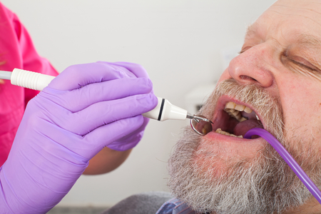 Elderly male patient in the dentist chair while young doctor doing dental treatment