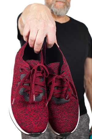 Close up picture of man holding stylish sporty shoes on isolated background