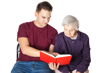 Handsome young man reading a novel with elderly disabled grandmother on isolated background Stock Photo