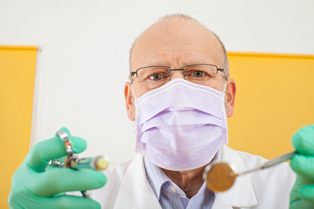 Close up picture of senior male dentist holding dental instruments - anesthesic syringe and mirror Banque d'images