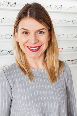 Portrait of beautiful smiling woman in optical store buying eyeglass to correct vision