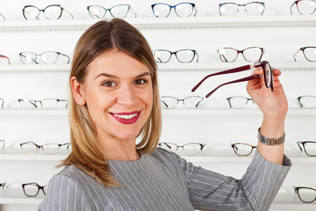 Attractive young woman choosing eyeglass frame in an optical store, fashion & style Stock Photo
