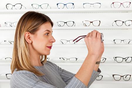 Beautiful young woman choosing eyeglass frame in an optical store, fashion & style