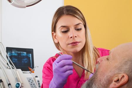 Giovane dentista femminile che esamina paziente maschio maturo con sonda parodontale