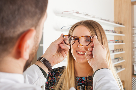 Friendly male ophthalmologist choosing eyeglass frame for beautiful young woman in an optical store Standard-Bild