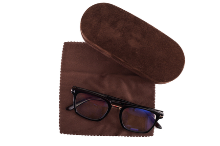 Close up picture of corrective eye glasses and brown case on isolated background