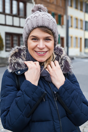 Cheerful female tourist smiling to the camera in the city of Interlaken, swiss alps