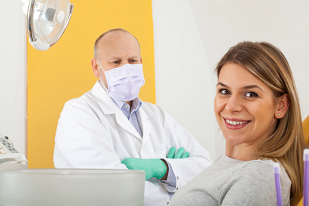 Attractive female patient smiling at the camera in dentist chair, mature male doctor with mask in behind