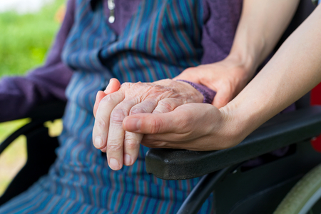 Close up picture of carer holding elderly womans shaking hands, sitting in a wheelchair - Parkinson disease