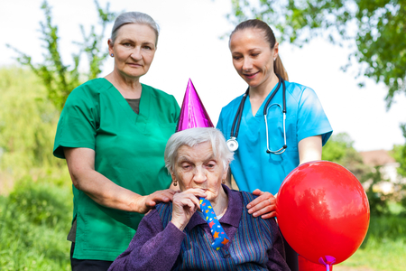 Senior disabled woman in a wheelchair celebrating birthday with friendly female caregivers outdoor Archivio Fotografico