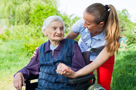 Senior invalid woman spending time outdoor with friendly young caregiver Stock Photo