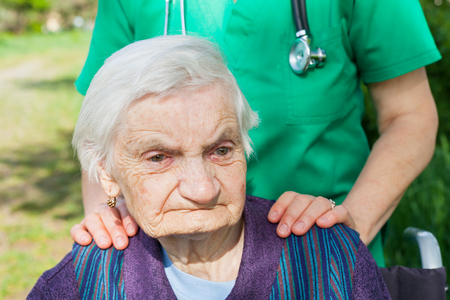 Portrait of elderly disabled woman sitting in a wheelchair spending time outdoor with friendly nurse