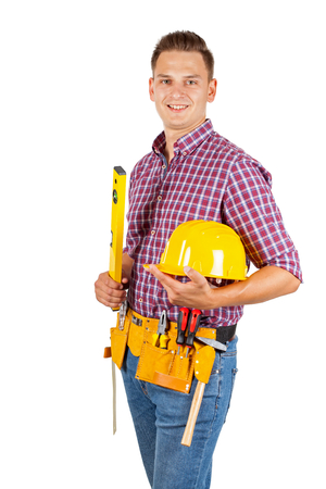 Attractive young repairman with yellow helmet and tool belt on isolated background Stock Photo