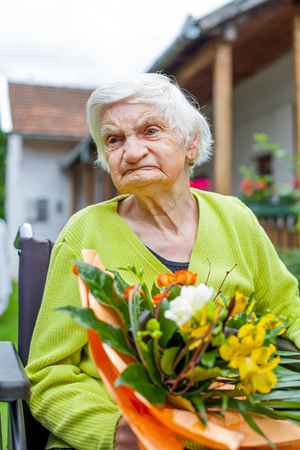 Disabled elderly woman sitting in wheelchair, receiving a flower bouquet for her birthday Stock Photo