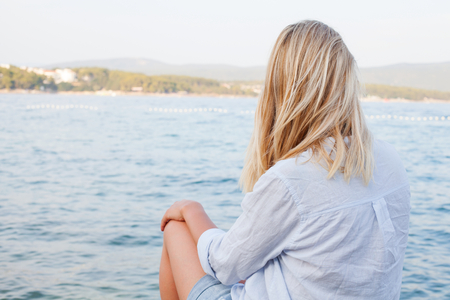 Young woman relaxing by the seaside, looking at the waves
