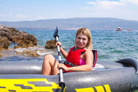 Happy young woman kayaking in the adriatic sea, near by Krk island, Croatia