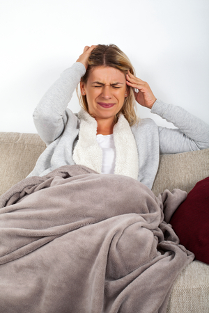 Blonde woman having headache, sitting on the couch wrapped in a grey blanket