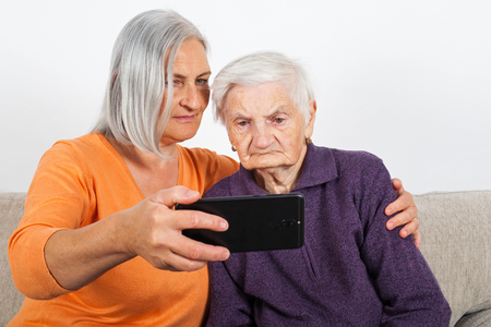 Elderly woman taking a selfie with smiling caregiver Stock Photo