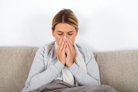 Picture of a sick young lady sitting on the couch and blowing her runny nose Imagens