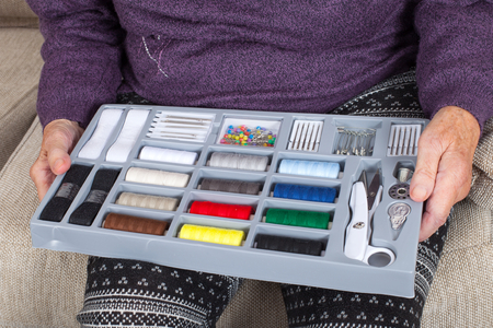 Elderly woman holding a sewing kit with colored twisted yarn
