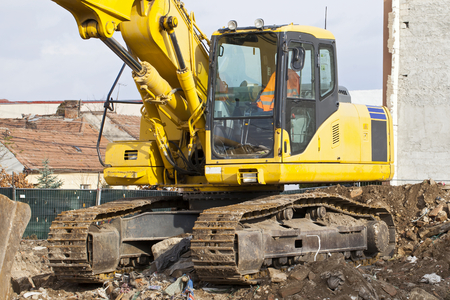 Picture of a hydraulic yellow excavator working on field