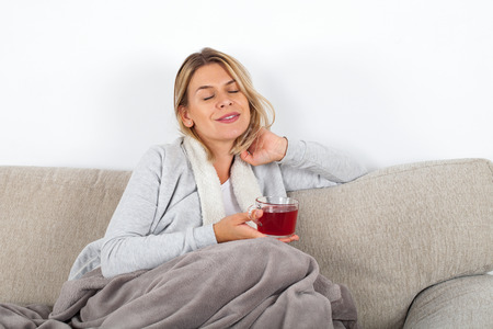 Beautiful woman relaxing on the sofa and drinking hot tea, wrapped in a grey blanket
