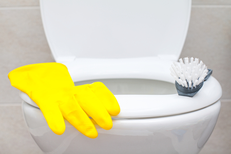 Colorful bathroom cleaning products and yellow rubber gloves, white lavatory pan in the background