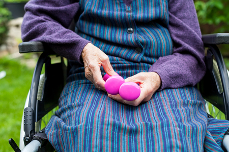 Handicapped elderly woman sitting in wheelchair,  holding dumbbell in her wrinkled hands Stock Photo