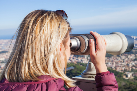 Blond female tourist looking into binoculars at the top  of Tibidabo - Panoramic view of Barcelona, Catalunia Banco de Imagens