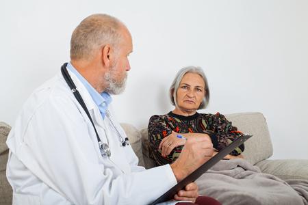 Medico con appunti che diagnostica un paziente anziano a casa Archivio Fotografico