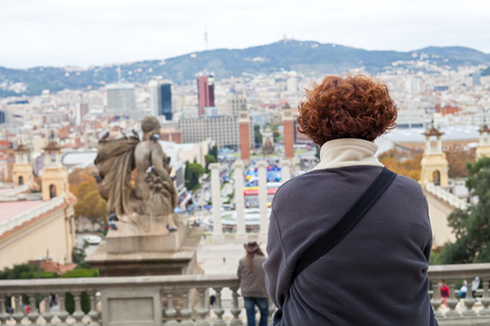 Back view of single middle aged woman looking at Barcelonas city center. Panorama. City break. Alone