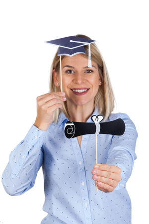 Confident young woman holding university diploma and academic cap, smiling to the camera on isolated background
